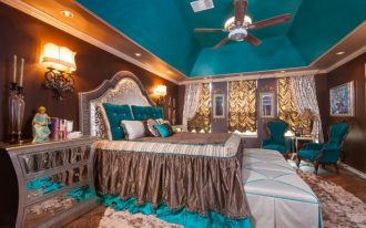 teal and brown teal ceiling brown walls teal tufted armchairs master bed windows ceiling fan area rug wall sconces nightstands