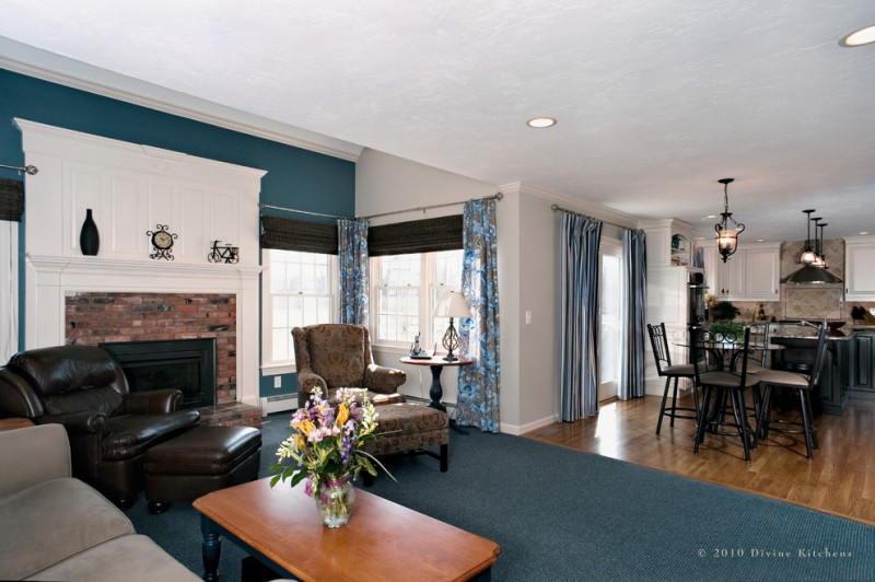 teal room teal wall large teal rug wood coffee table beige couch dark brown leather armchair footstool lighting fireplace blue chairs