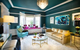 teal room yellow sofa chandelier black table lamp side table white shag rug wall decorations window bench blue chair round glass table