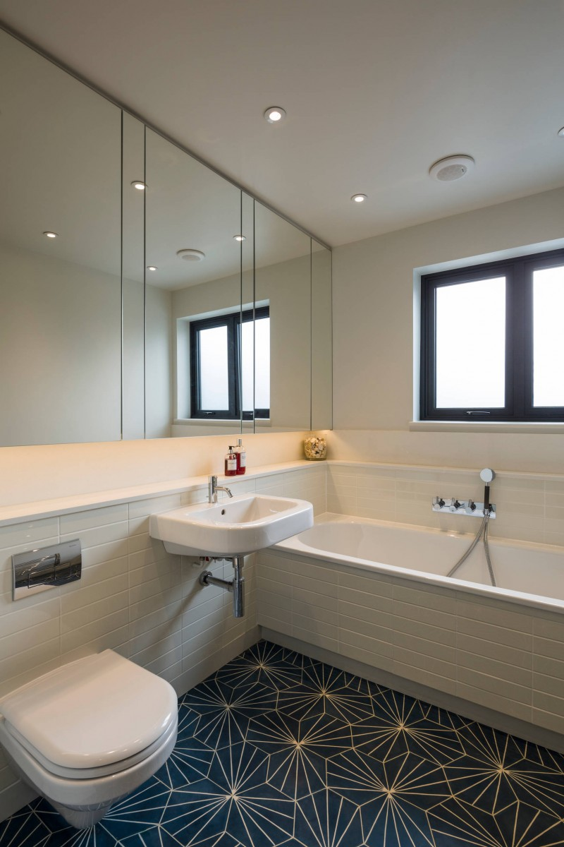 wall mirror tiled tub tiled wall tiled floor wall mounted toilet wall mounted sink recessed lights bathtub (1)