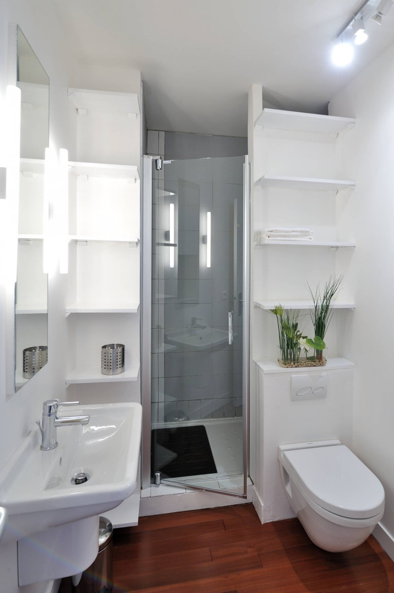 wall mounted toilet open cabinet wall mounted shelves white sink alcove shower mirror glass door wall lights wood floor
