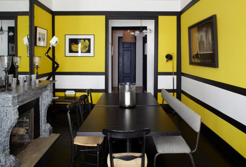 yellow dining room black floor black dining table and chairs artworks mirror fireplace grey fireplace mantel grey bench floor lamps