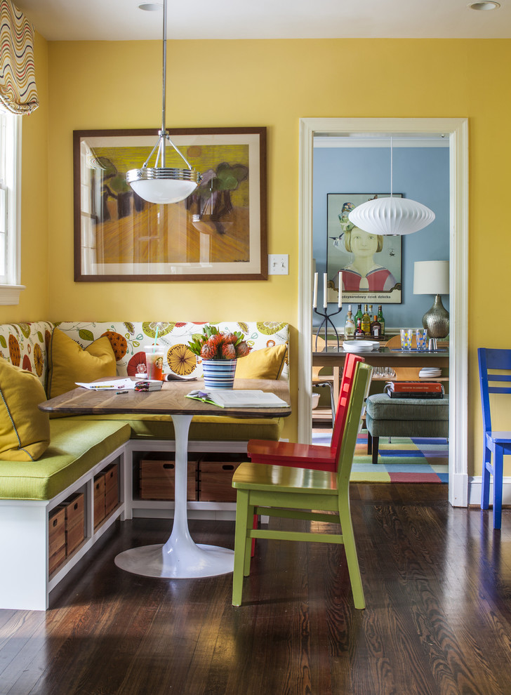 yellow dining room corner bench pedestal table with wood top wood flooring pendant lamp window with colorful window shade artwork