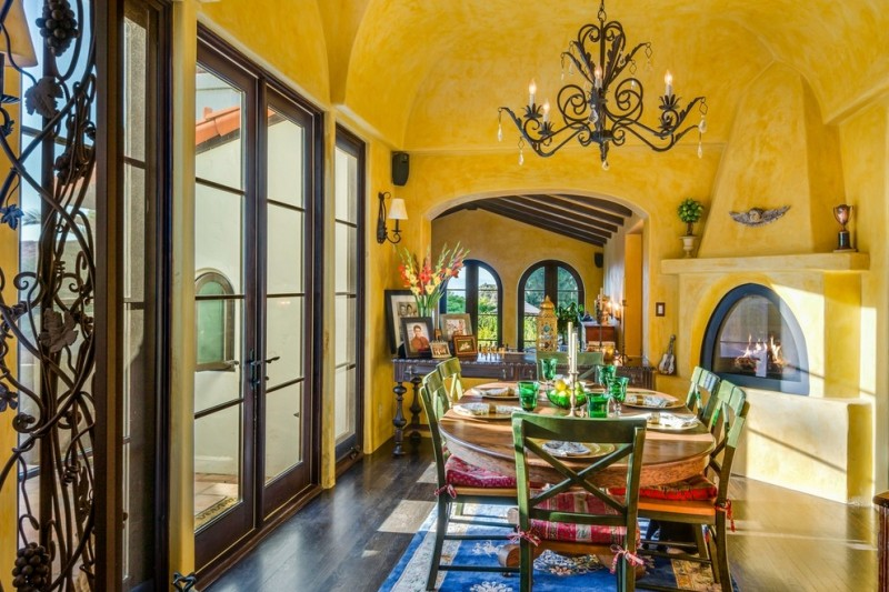 yellow dining room rustic chandelier glass doors glass windows glass dining table green dining chairs blue area rug fireplace