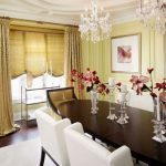 Yellow Dining Room Wooden Oval Dining Table White And Yellow Dining Chairs Crystal Chandeliers Yellow Walls Curtains And Shade Art Flower