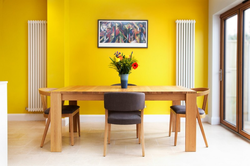 yellow dining room yellow wall sliding glass doors artwork beige floor tiles minimalist wood dining table and chairs with black cushions