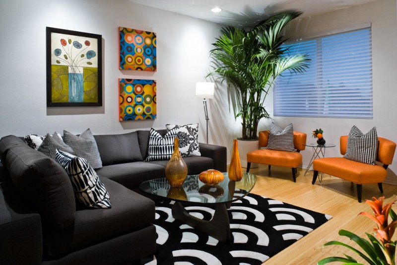 black white area rug colorful wall decor grey sofa noguchi coffee table indoor plant orange leathered chairs side table