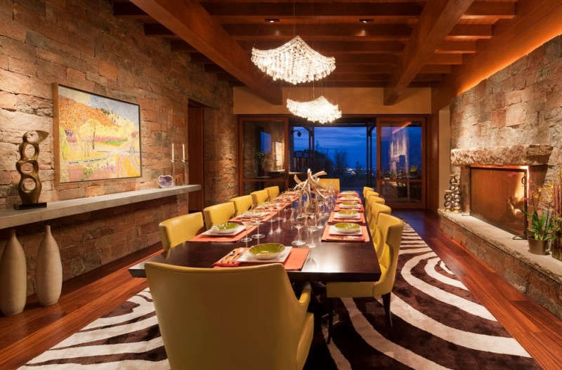 black white area rug yellow leathered dining chairs large wooden dining table crystal chandeliers fireplace brick walls wood flooring