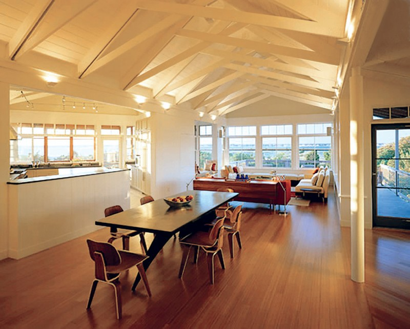 cathedral ceiling lighting wall sconces wood beams beadboard ceiling couches dining table and chairs windows wood flooring