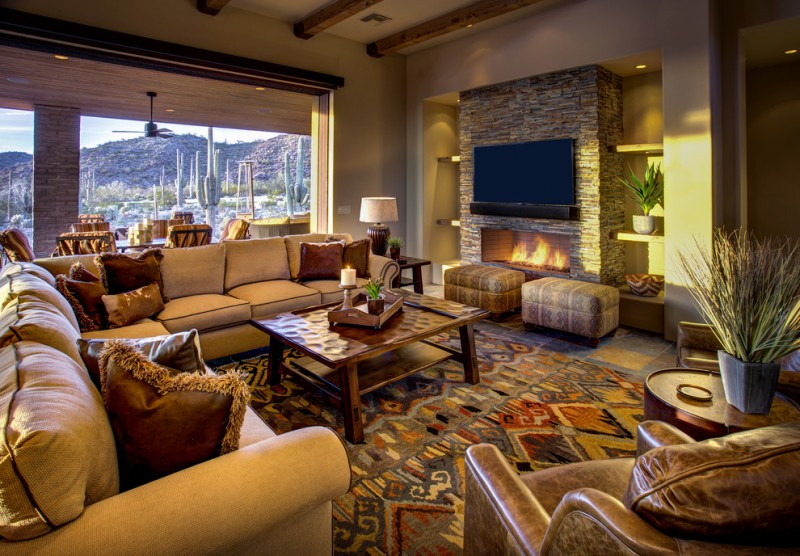 custom coffee table southwestern carpet beige wall beige sofa brown pillow leather couch ottoman fireplace exposed beams floating shelves ceiling fan