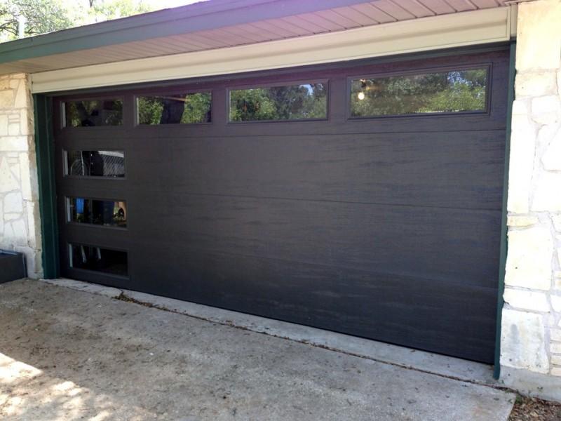 dark garage door metal door glass window stone wall driveway