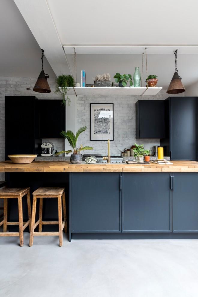flat panel cabinet black cabinet island wooden bar stools wooden countertop tiled backsplash concrete floor pendant lights hanging shelf
