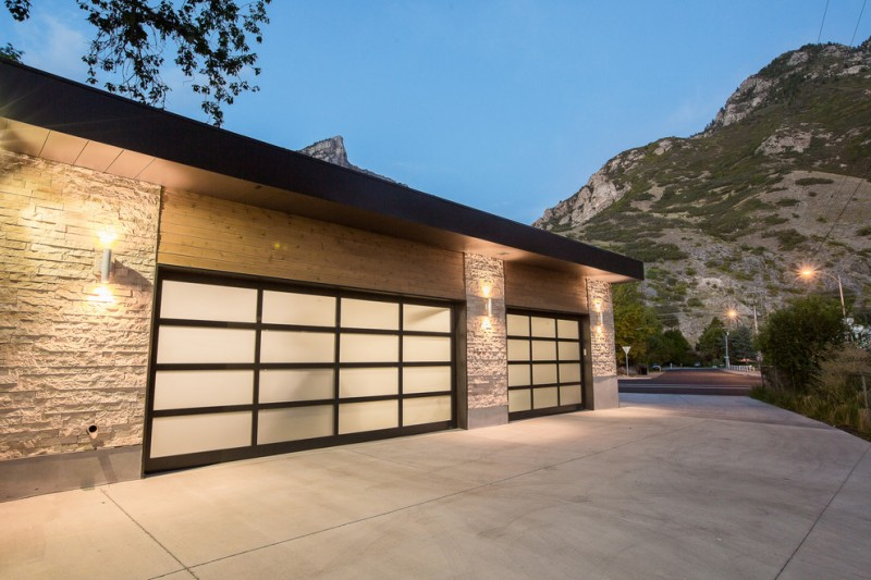 frosted door black trim stone wall eaves wall lights concrete driveway 3 car garage