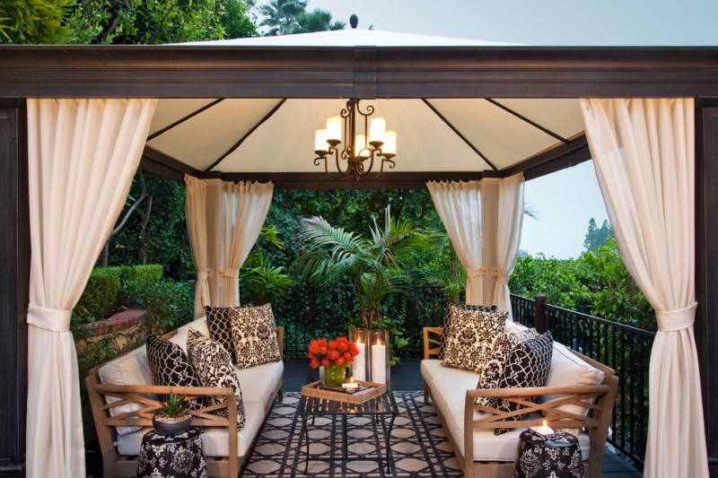 gazebo lighting antique chandelier black white rug and pillows wooden outdoor seating with white cushions iron table curtains