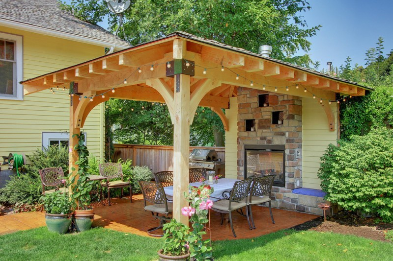 gazebo lighting string lights metal branches fireplace iron chairs dining table brick accent wall wood wall orange floor tile flowers