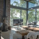 Gray And Brown Living Room Glass Walls Fireplace Oval Wooden Coffee Table Grey Sofa Pillow Black Frame Stone Accent Wall