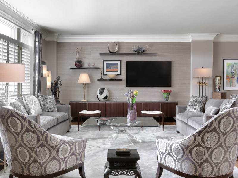 gray and brown living room gray sofas brown cabinet wall mounted shelves patterned armchairs gray rug grey curtains