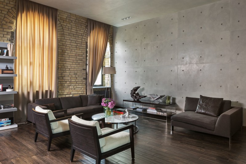 gray and brown living room gray wall exposed brick wall wood floor brown sofa and couch armchairs round coffee table curtains