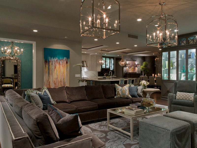 gray and brown living room gray wall gray armchair and ottoman brown couch glass coffee table artwork chandelier showcase cabinets