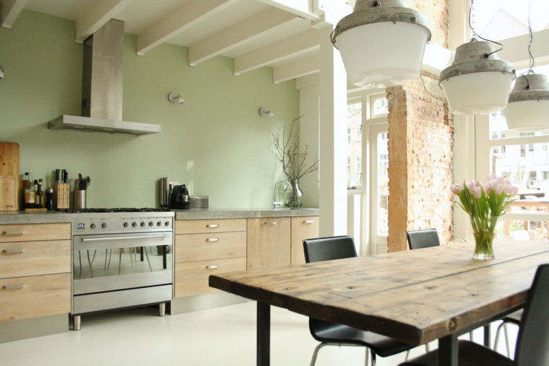 pastel kitchen green wall light wood cabinets undermount sink wooden dining table black chairs pendants brick wall white ceiling