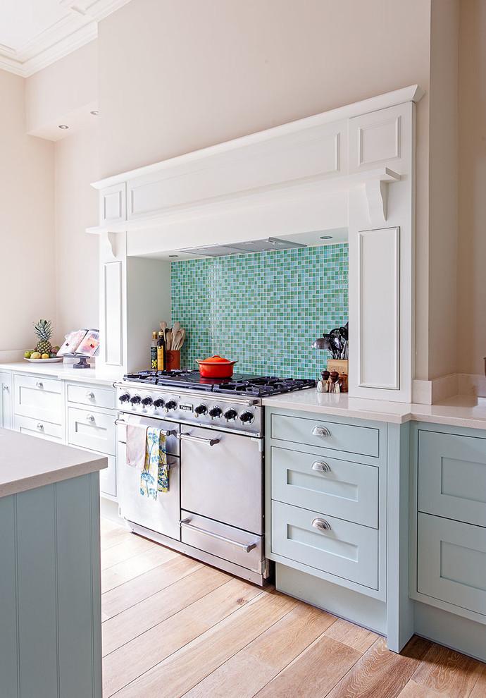 pastel kitchen pink wall wood flooring blue cabinets blue and green mosaic backsplash white countertop wood flooring