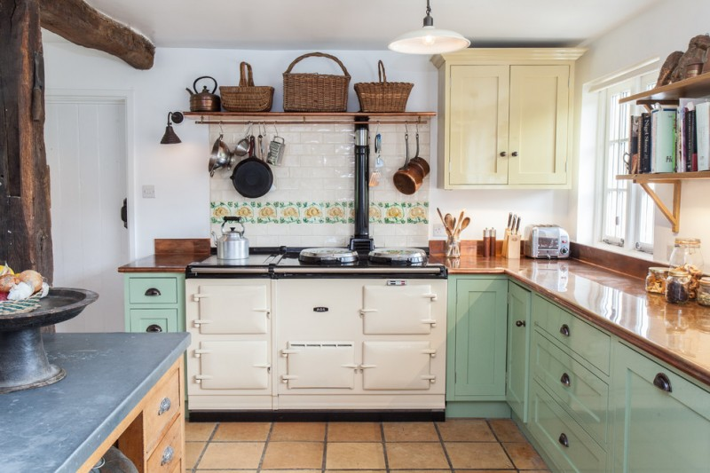 pastel kitchen traditional cabinets brown gloss countertops white backsplash tile with flower patterns wall mounted wooden shelves