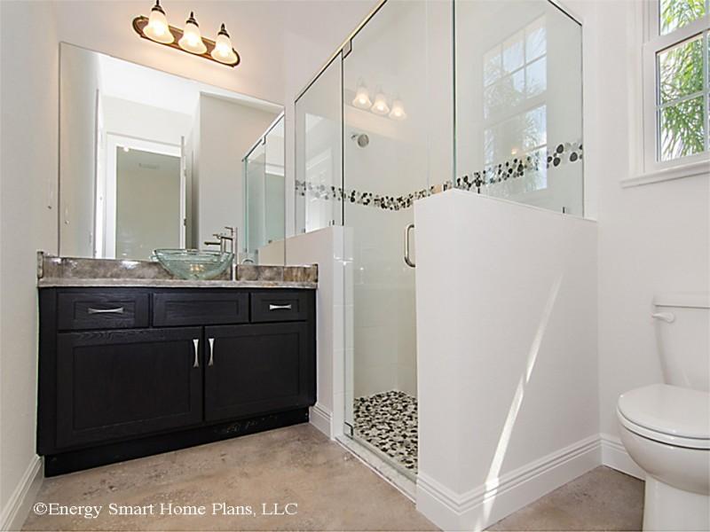 peble floor white wall one piece toilet glass siding black cabinet granite countertop vessel sink mirror pendant lights