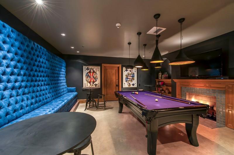pool table purple felt bar stools long bench headboard round coffee table pendant lights tiled fireplace mini bar wall decoration TV