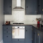 Raised Cabinet Dark Cabinet Tiled Backsplash Black Countertop Stainless Steel Hood Pendant Light