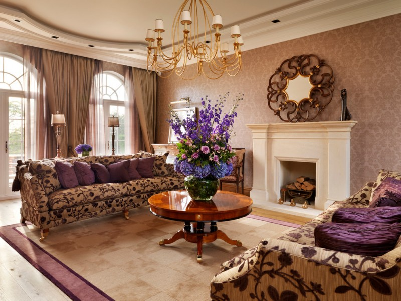 round pedestal coffee tables chandelier flowers brown floral sofas purple throw pillows fireplace windows brown curtains area rug mirror