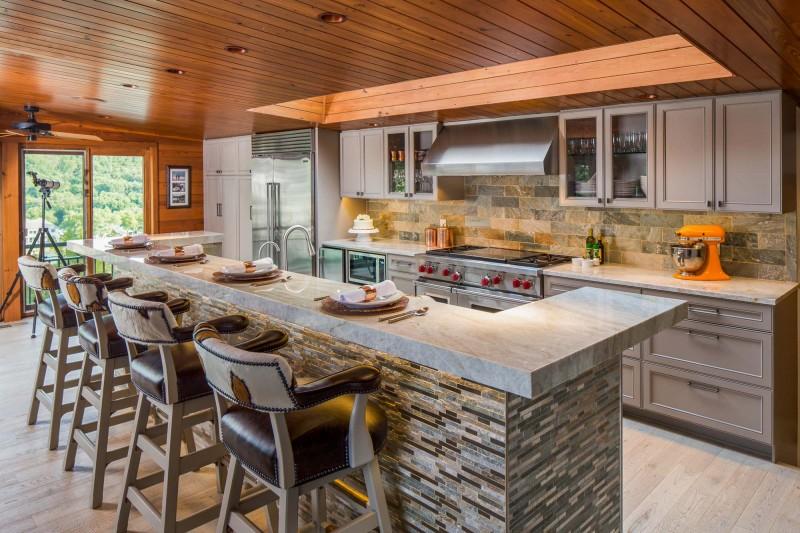 slate backsplash slate island wooden ceiling wooden floor granite countertop bar stools shaker cabinet hood ceiling fan wooden wall