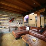 Sloped Ceiling Brick Wall Tan Wall Slate Floor Floating Shelves Brown Leather Sofa Wooden Desk Exposed Beams