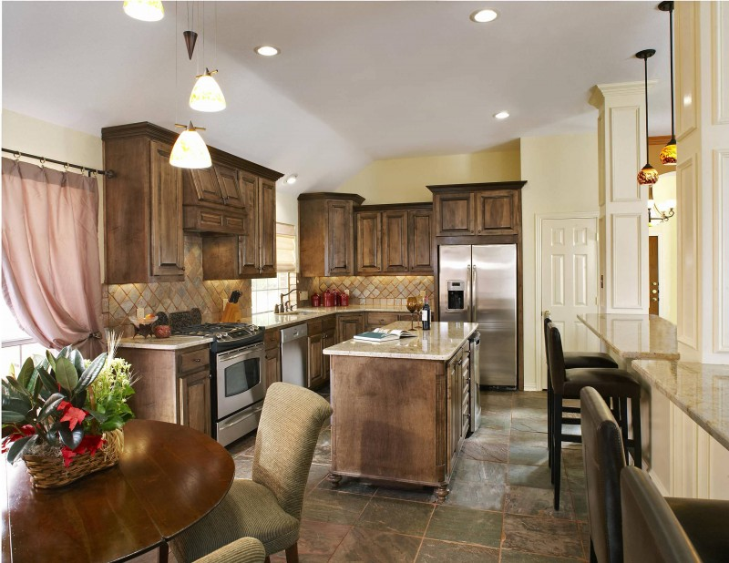 stained cabinet slate backsplash slate floor island granite countertop stainless steel appliances pendant lights rounded dining table bar stools pink curtain