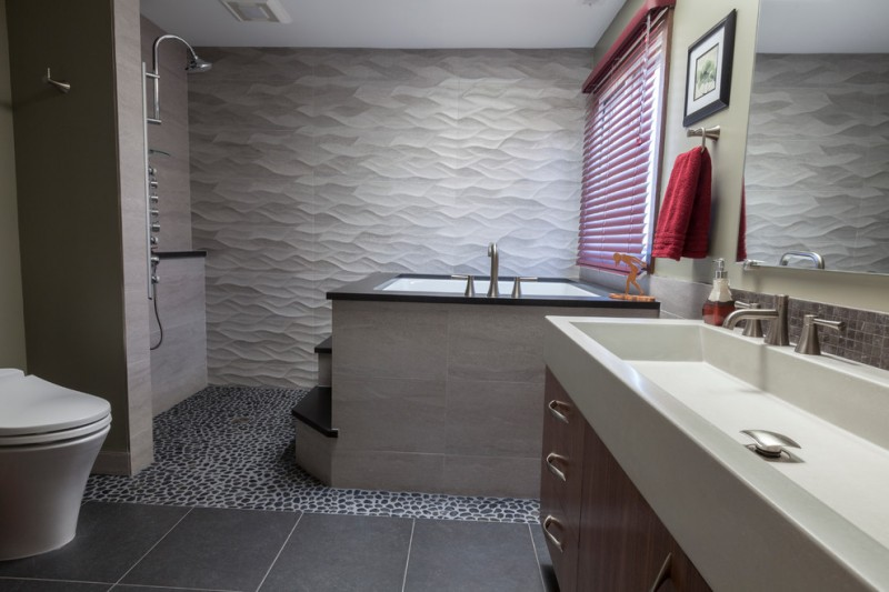 stone floor Japanese tub porcelain floor two piece toilet wood cabinet through sink wallpaper tiled wall stairs