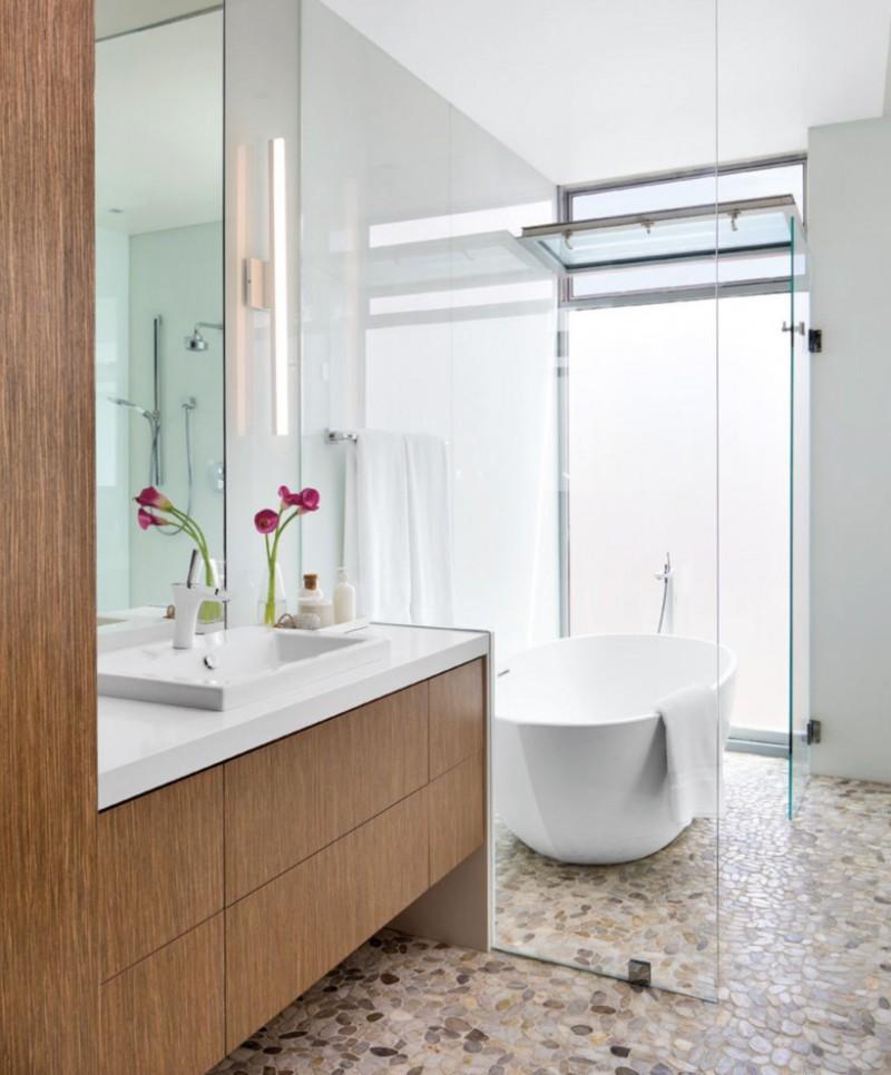 stone floor medium tone cabinet flat penel cabinet drop in sink mirror glass siding freestanding tub open window white wall