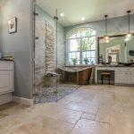 Stone Floor Slate Wall Blue Wall White Cabinet Mirror Freestanding Tub Pendant Lights Vessel Sink Glass Door Granite Countertop Arched Window
