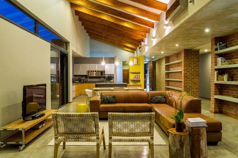 tan leather sofa rug area rattan chair logs TV stand brick wall kitchen sloped ceiling built in shelves pendant lights recessed lights