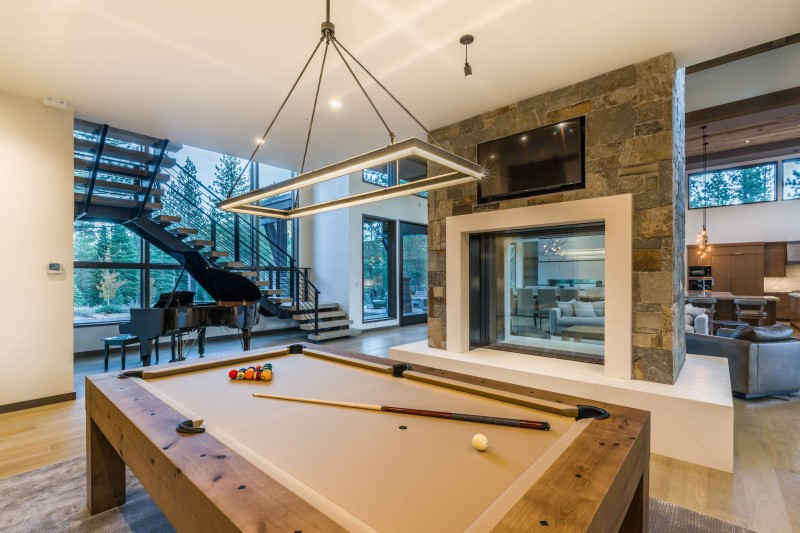 two sided fireplace concrete fireplace two way TV pool table hanging lamp piano staircase sofa oversized glass window