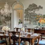 Victorian Dining Table Wall Mural Crystal Chandelier Blue Cushioned Chairs Candle Holder Flowers Glass Vase Area Rug
