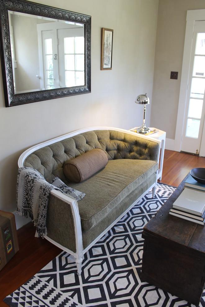 vintage settee geometric pattern rug black framed mirror side table wooden coffee table throw table lamp