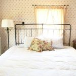 70s Bedroom 1970 Wallpaper Pattern Black Iron Headboard White Bedding Floral Pillow Wooden Nightstand Table Lamp Window