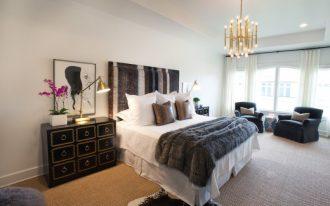 70s bedroom chandelier grey stripe headboard grey fur throw blanket white duvet pillows armchairs curtains cowhide rug