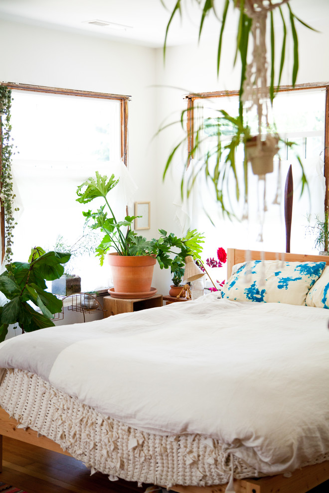 70s bedroom white duvet wooden bed colorful pillows indoor plants white wall wooden side table windows wooden floor