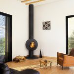 Freestanding Wood Burning Fireplace White Walls And Ceiling Sliding Glass Doors With Black Frames Leathered Armchairs Small Table Artwork
