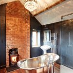 Freestanding Wood Burning Fireplace Wood Flooring Rustic Bathtub Tub Faucet Crystal Chandelier Glass Shower Doors Brick Wall