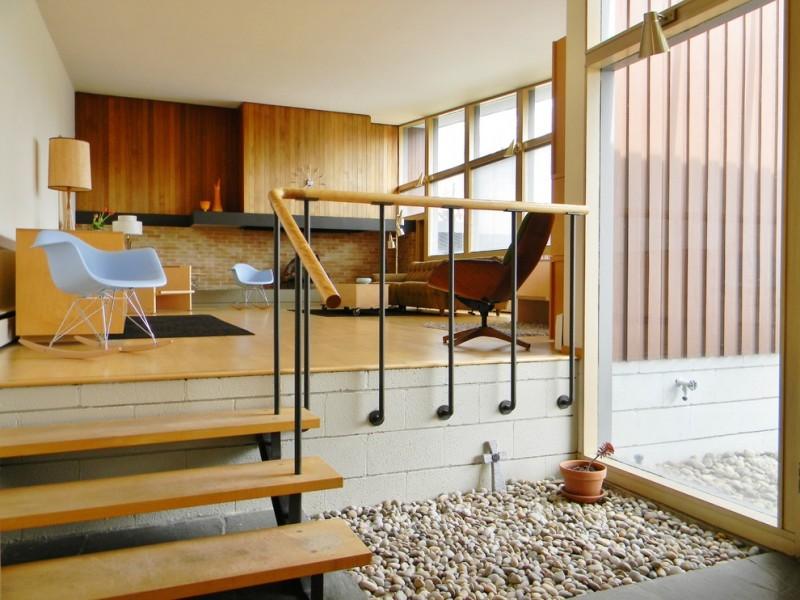 light wood floor brick wall flat panel wall floating shelf sofa coffee table plastic rocking chair stairs railing stone block stone outdoor glass window