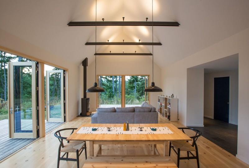 light wooden floor dining space gray sofa shelves hanging lights upward lights high ceiling fireplace glass window door wooden deck