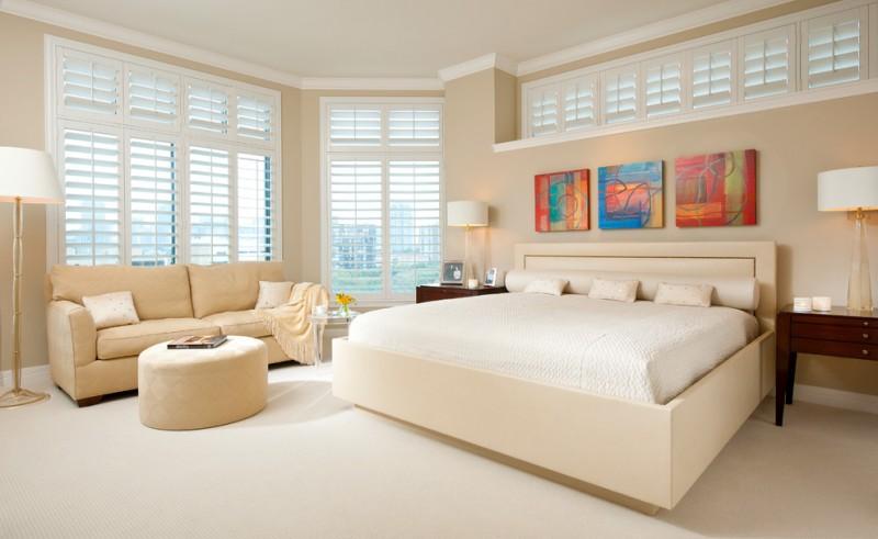 mansion master bedroom beige bed colorful artworks white table lamps nightstands beige sofa beige ottoman windows floor lamp