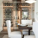 Modern Wine Cellar Beige Marble Wall Recessed Light Wine Racks Glass Doors White Chairs Wooden Table Area Rug