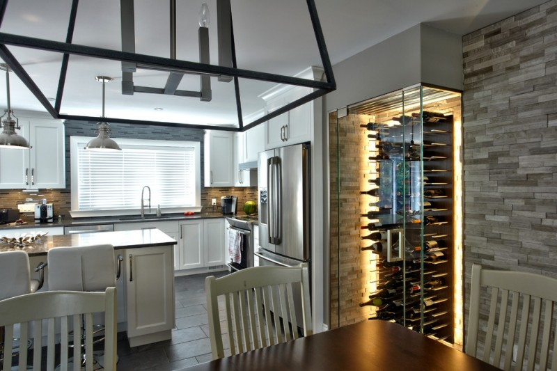 modern wine cellar glass wine cellar doors stone wall dining table chairs pendant lamps white cabinets barstools stove oven